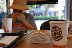 Onduidelijk beeldmotie van vrouw die hamburger eten en hete koffie drinken bij het snelle voedselrestaurant van Burger King royalty-vrije stock foto's
