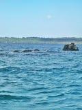 Ondulación del mar alrededor de la piedra del mar en el centro Fotografía de archivo