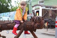 ONDULACIÓN PERMANENTE, RUSIA - 18 DE JULIO DE 2013: La niña se sienta a horcajadas en la escultura Kotofeich de la ciudad Imagen de archivo