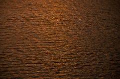 Ondulaciones en agua del oro Imágenes de archivo libres de regalías