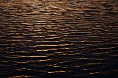 Ondulaciones en superficie del agua durante puesta del sol Foto de archivo libre de regalías