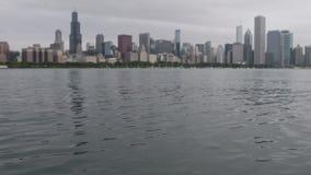 ondulaciones 4K en el lago Michigan con el horizonte de Chicago en fondo almacen de metraje de vídeo