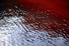 Ondulaciones rojas sangre en el agua imagen de archivo