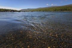 Ondulaciones tranquilas hermosas en la agua corriente con las piedras asombrosas de la parte inferior de río de la coloración imagen de archivo libre de regalías