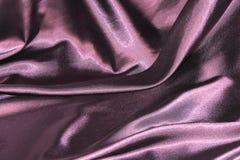 Ondulando dobras da tela da seda roxa Fotografia de Stock