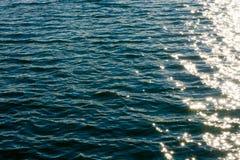 Ondulations de mer Fond lumineux L'eau vert-foncé Les vagues peu profondes et le soleil brillent sur l'eau Photo stock