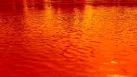 Ondulations sur l'eau, le vent Couleurs d'orange, jaunes et rouges lumineuses