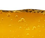 Ondulez d'un liquide jaune avec des bulles d'air sur le fond blanc Images stock