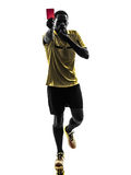 One african man referee standing showing red card  silhouette Royalty Free Stock Images