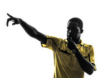 One african man referee whistling pointing  silhouette Stock Photos