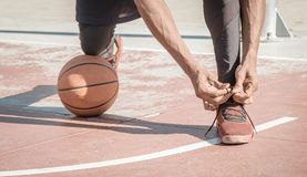 Afroamerican young man playing street basketball in the park is stock image