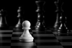 One against all - a black pawn with white chess pieces Royalty Free Stock Image