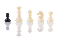 One against all - a black pawn with white chess pieces Stock Photos