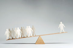 One against many. Men balanced on seesaw over a single man Royalty Free Stock Photos
