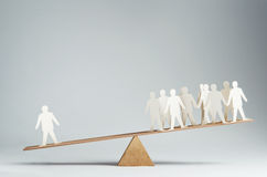 One against many. Men balanced on seesaw over a single man Stock Photography