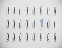 One against zeroes. Standing out from the rest. Unique paperclip shaped as number 1 stands out in a crowd of regular paperclips shaped like zeroes Royalty Free Stock Photography