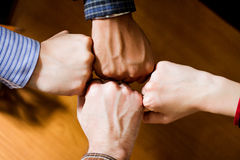 One for all. Four fists collide together forming a great team Stock Image