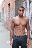 One amazing African man with muscular male sensual topless body with strong cool 6 pack abdominal and athletic chest. Dressed in just jeans posing on graffiti Stock Images