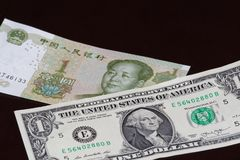 One american dollar banknote above one Chinese yuan on black background. One american dollar banknote is above one Chinese yuan on black background stock images