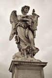 One of the angels at the Sant' Angelo bridge in Rome, Italy. One of the angels at the famous Sant' Angelo bridge  over castle background in Rome, Italy Stock Image
