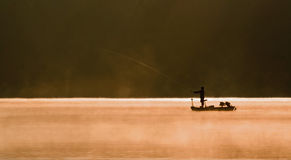 One Angler Fishing on A Lake. One angler fishing on a misty sunlit lake Royalty Free Stock Images