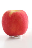 One apple a day keeps the doctor away. An apple above tablets are isolated stock photography