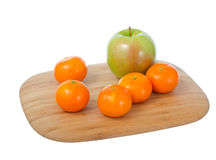 Fruits on cutting board. One apple and some mandarines on wooden cutting board isolated on white background Royalty Free Stock Photo