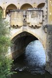 One arch of an old french bridge over the river. In the summer day Royalty Free Stock Photography