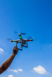 One arm touching flying quad copter Stock Photography