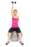 One Arm Triceps Extensions on Fitness Ball. Young woman doing Seated Dumbbell One Arm Triceps Extensions on Fitness Ball, phase 2 of 2 Stock Photo