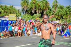 One of the artist of Bloco Orquestra Voadora walking with naked torso carrying his stilts on his shoulder, Carnaval 2017 Stock Photography