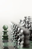 The one as he is. One pawn staying against full set of chess pieces Royalty Free Stock Photos