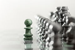 The one as he is. One pawn staying against full set of chess pieces Stock Images