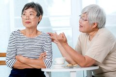 One Asian elderly woman try to reconcile to the other one during the tea time near balcony in the house royalty free stock photos