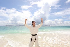 One Asian man playing with taekwondo outdoor. Young adult man with black belt practicing a Kata on the beach Royalty Free Stock Image
