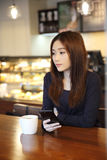 One Asian woman thinking with smart phone. In close up Stock Photo