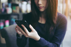 One Asian woman thinking with smart phone. In close up Stock Photography