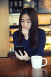 One Asian woman thinking with smartphone Stock Images