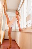 One athletic, beautiful flexible blond girl elegant young woman raised leg in split parallel to the wall in pajamas. Beautiful flexible blond girl elegant young Stock Photography