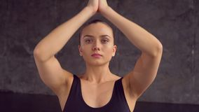 One attractive 20s female person sitting in lotus position on matting and breathing inside of yogas studio closeup. Strong sportswoman concentrated making stock video