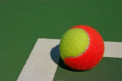 One ball in a corner. Yellow-red balls on a green tennis court Stock Photo