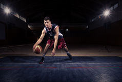 One basketball player dribble ball. One young adult man, basketball player dribble ball, dark indoors basketball court royalty free stock photos