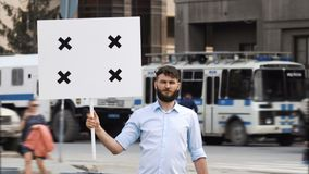 Young adult protester on the background of a police car at a rally with a banner. One bearded european guy on the background of a police car holds a banner in