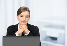 One beautiful business woman with laptop in the office. And printer as a background Royalty Free Stock Photography