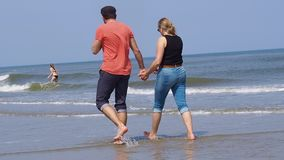 One beautiful couple man and woman in jeans shorts walking on tropical beach holding hands. They go to the water barefoot on sand. Love, romantic and vacation stock video