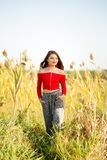 One beautiful female caucasian high school senior girl in red crop top sweater. Walking outside in a farm field summertime royalty free stock image