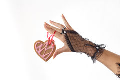 One beautiful female hand in black lace glove holds a heart shaped gingerbread cookie on red ribbon Stock Photography
