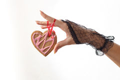 One beautiful female hand in black lace glove holds a heart shaped gingerbread cookie on red ribbon. Against white beackground, horizontal view. Valentine`s day stock photography