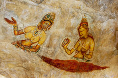 One of the beautiful frescoes at Sigiriya Rock in Sigiriya, Sri Lanka. Dating from around the 5th century, there is debate over whether the figures depict King Stock Photo