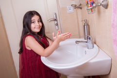 One beautiful little middle eastern arab girl with red dress is washing her hands in the bathroom. Royalty Free Stock Image